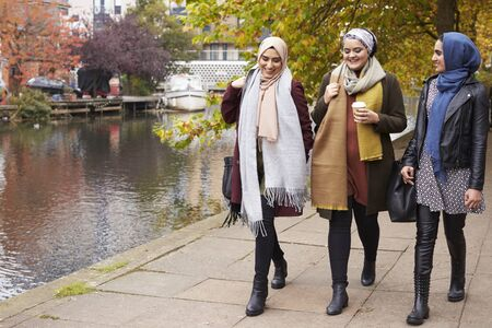British Muslim Female Friends Walking By River In City Stock Photo