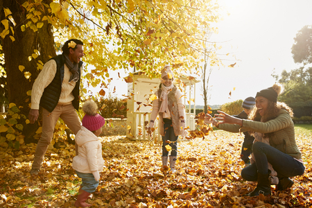 Family Playing With Autumn Leaves In Garden Together