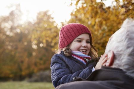 秋の散歩に抱きしめる孫娘を祖父します。
