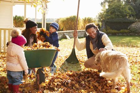 Bambini che aiutano i genitori a raccogliere foglie d'autunno in giardino