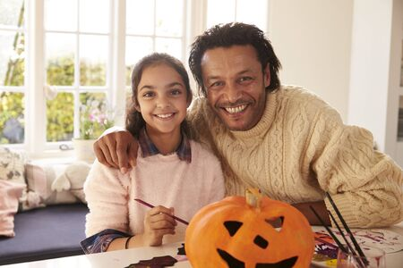 Father And Daughter Making Halloween Decorations At Home Stock Photo