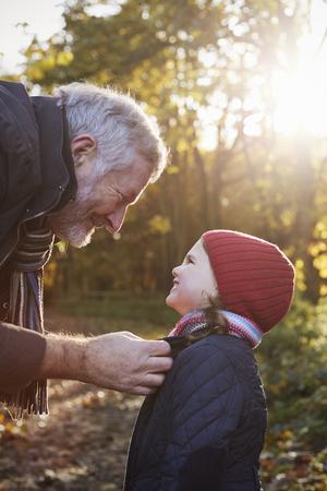 秋の散歩の抱き合わせの孫娘のスカーフを祖父します。