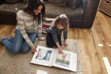 Mother And Daughter At Home Looking Through Photo Album