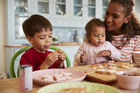 biscuits: Mother And Children Decorating Cookies At Home Together