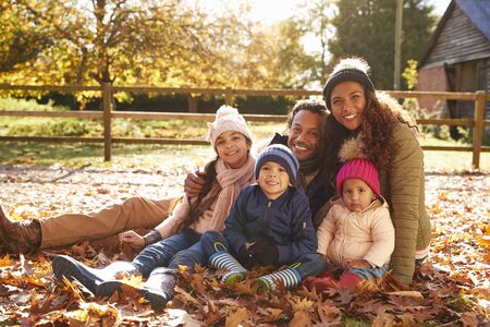 Portrait Of Family On Walk Sitting In Autumn Leaves Stock Photo