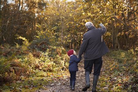 祖父と孫娘の秋の散歩を楽しんで