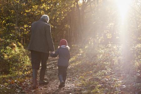 Großvater Und Enkelin Genießen Herbst Spaziergang Standard-Bild
