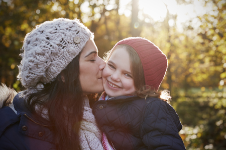 smile close up: Mother Cuddling Daughter On Walk In Autumn Countryside