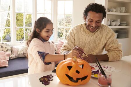 front desk: Father And Daughter Making Halloween Decorations At Home Stock Photo