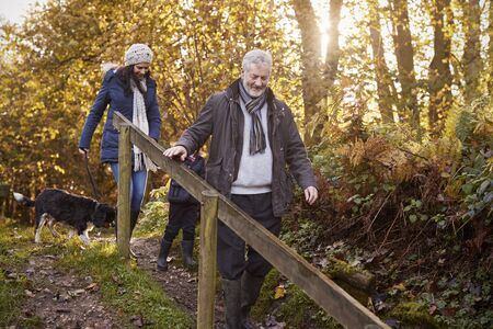 3 4 years: Multi Generation Family Take Dog For Walk In Fall Landscape Stock Photo