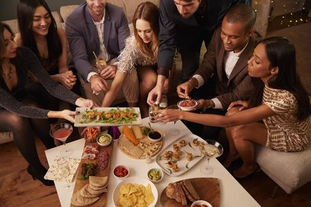 Top view of group of friends enjoying drinks and snacks at a party
