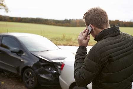 Un homme appelle à signaler un accident de voiture sur une route de campagne Banque d'images - 78080608