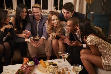 Group of friend enjoying drinks and snacks at party