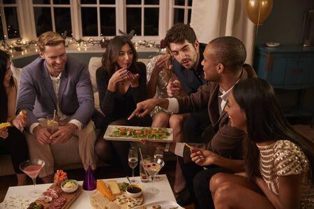 Group of friends enjoying drinks and snacks at party Stock Photo