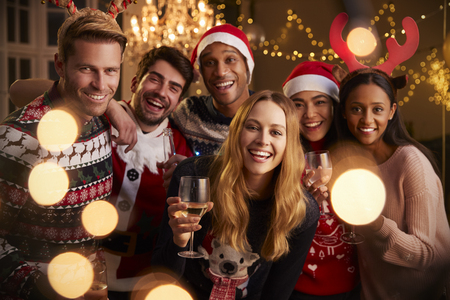 Portrait of group of friends in festive jumpers at Christmas party