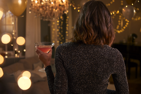 Rear view of a woman holding a drink at a cocktail party