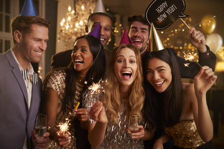 Group of friends celebrating at New Years party together Stock Photo