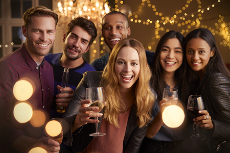 Group portrait of friends with drinks enjoying house party