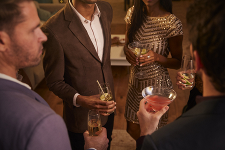 singaporean: Group of friends holding drinks and chatting at a cocktail party