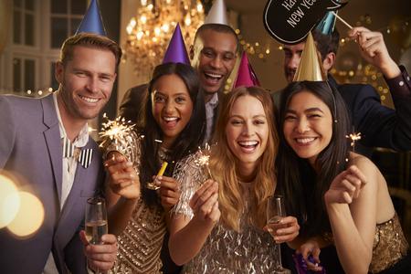 Groep vrienden die bij de partij van het Nieuwjaar samen vieren Stockfoto