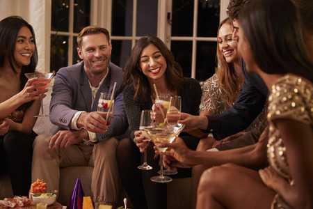 Friends toasting with drinks as they celebrate at a party together Stock Photo