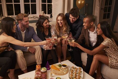 Group of friends enjoying snacks and drinks at a party together