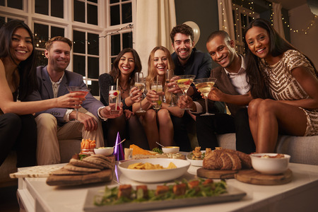 Portrait of friends with drinks and snacks at party