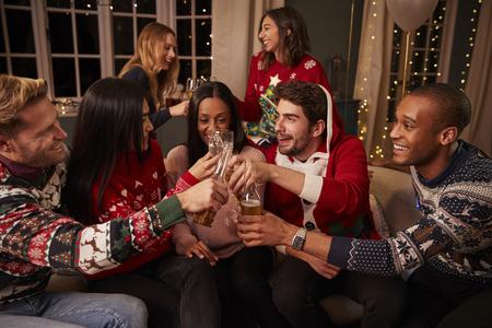 축제 점퍼에있는 친구들이 크리스마스 파티에서 축하 해요. 스톡 콘텐츠 - 79526439