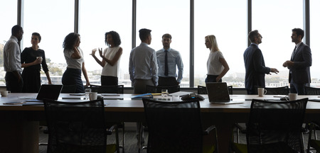 Businesspeople Stand And Chat Before Meeting In Boardroom