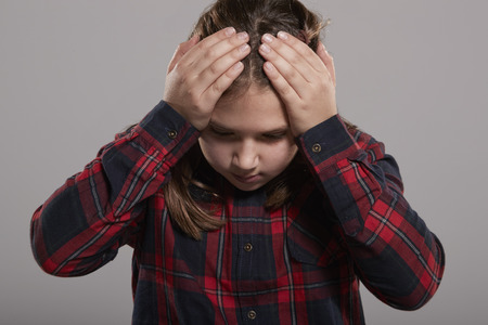 Ten year old girl holding head in frustration, waist up