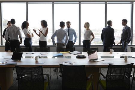 Ondernemers staan en chatten vóór vergadering in directiekamer