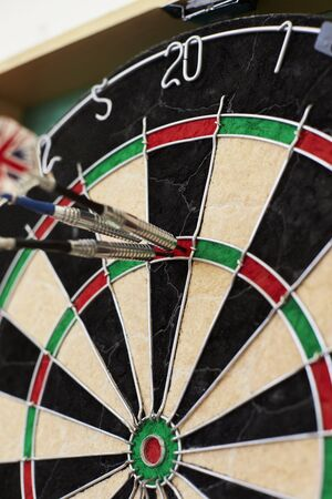 Close Up Of Dartboard With Three Darts In Treble Twenty