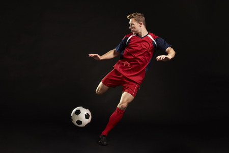 Professional Soccer Player Shooting At Goal In Studio Stock Photo