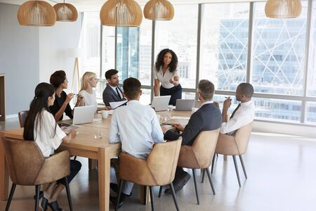 Businesswoman Stands To Address Meeting Around Board Table Reklamní fotografie