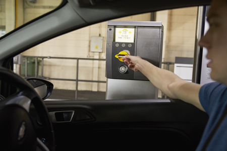 Driver Collects Ticket From Machine In Car Park