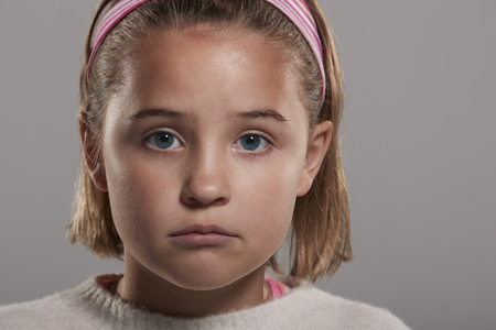 nine year old: Sad nine year old girl looking to camera, close up head shot