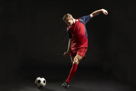 Jugador de fútbol profesional disparando a meta en estudio Foto de archivo