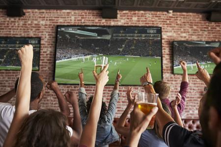 Rear View Of Friends Watching Game In Sports Bar On Screens Foto de archivo