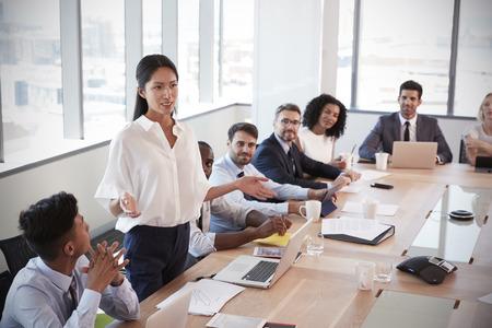 ボードのテーブルを囲んでの会議に対処するため立っている実業家