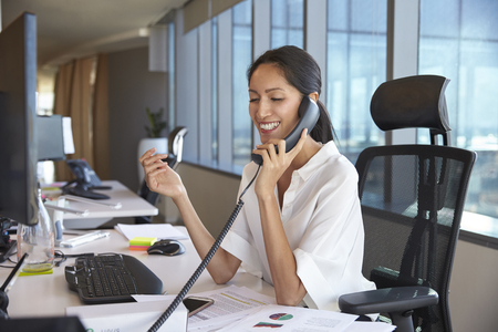 Businesswoman Making Phone Call Sitting At Desk In Office