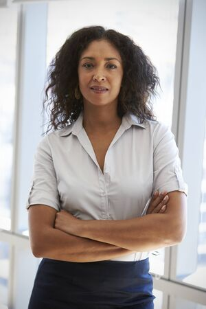 forties: Portrait Of Businesswoman Standing By Window In Office Stock Photo