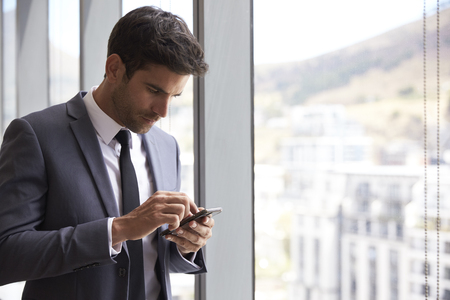 work: Businessman Checking Messages On Mobile Phone Stock Photo