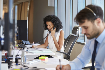 Businesswoman On Phone At Desk In Busy Office