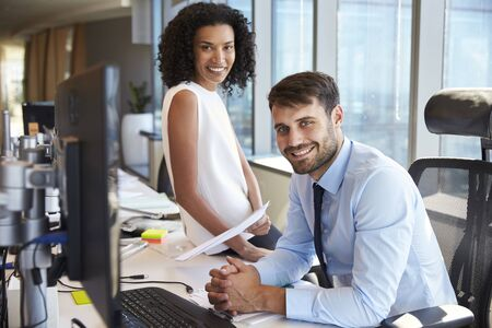 Portrait Of Businesspeople Working At Office Desk Together