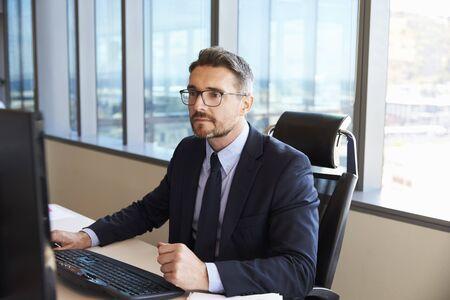 コンピューターを使用してオフィスで机に座っているビジネスマン 写真素材