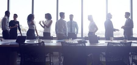 ビジネスマンのスタンドと会議室での会議の前にチャット 写真素材