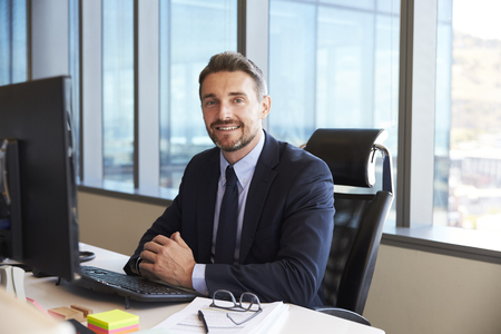 Portrait Of Businessman At Office Desk Using Computer Stock Photo