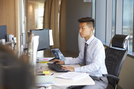 Young Businessman Sitting At Desk In Office Using Computer