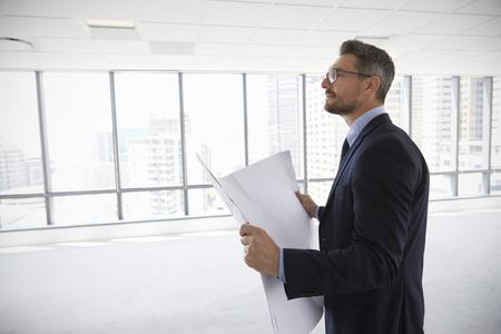 男性建築家の計画を見て現代の空オフィス