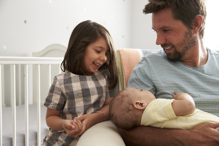 three months old: Father With Daughter And Newborn Son In Nursery Stock Photo